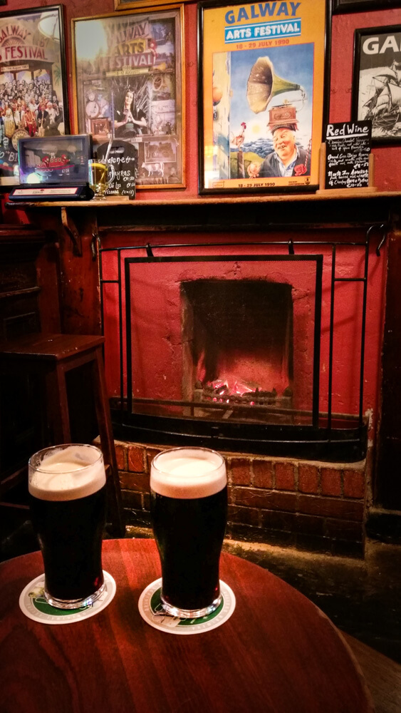 Ireland Galway Tigh Neachtain pub with two pints of Guinness in front of fireplace