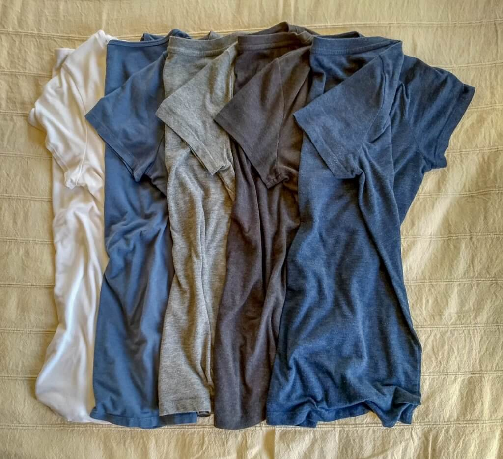 Packing t-shirts in blue and gray for trip