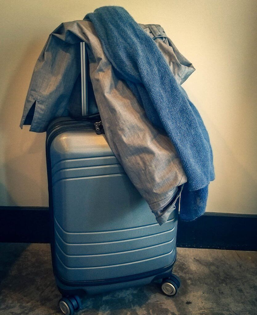 grey hard-sided luggage with jacket and blue scarf