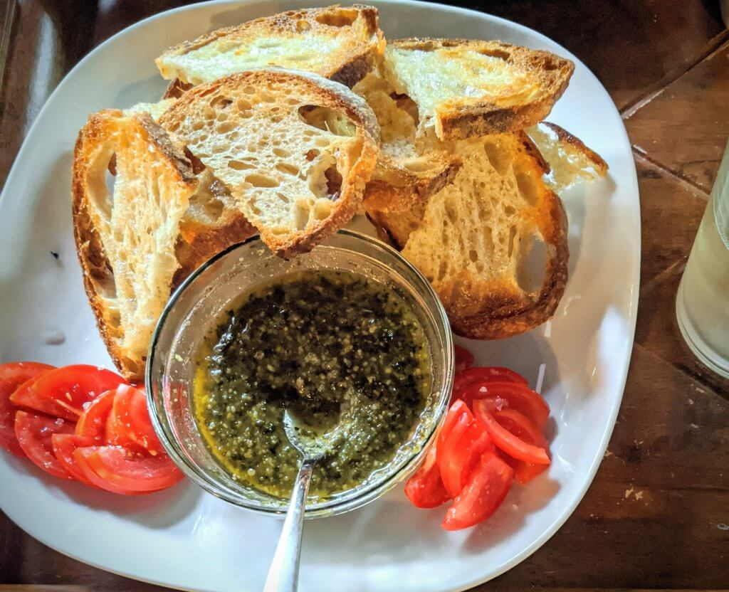 Basil pesto, bread and tomato on a plate
