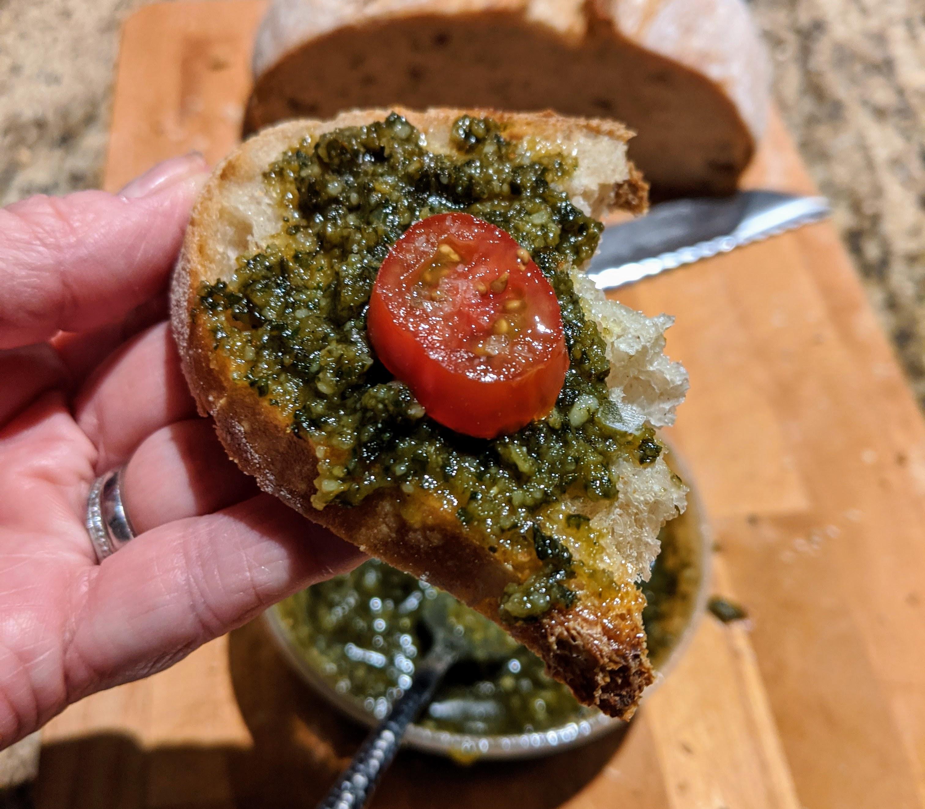 Basil pesto, bread and tomato in hand